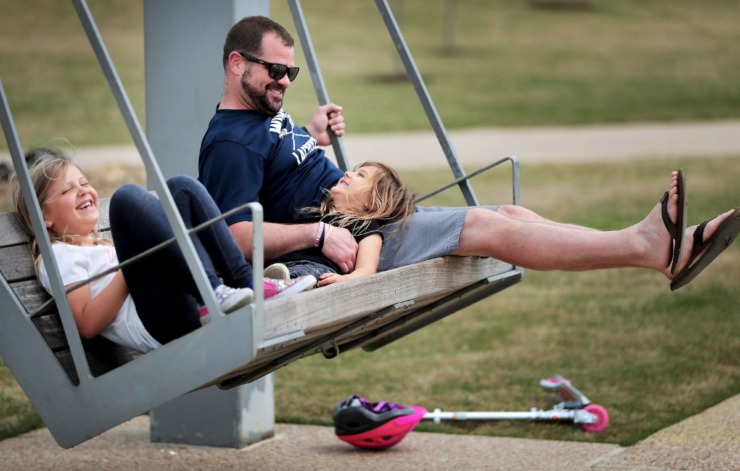 <strong>Ian Hill relaxes with his daughters Abigail (left) and Lucy at Shelby Farms as Memphians practice social distancing during workouts, dog walks and bike rides either alone or in small groups on April 4, 2020 after concerns over reports of people congregating in city parks, caused Mayor Jim Strickland to issue new restrictions this week.</strong> (Jim Weber/Daily Memphian)