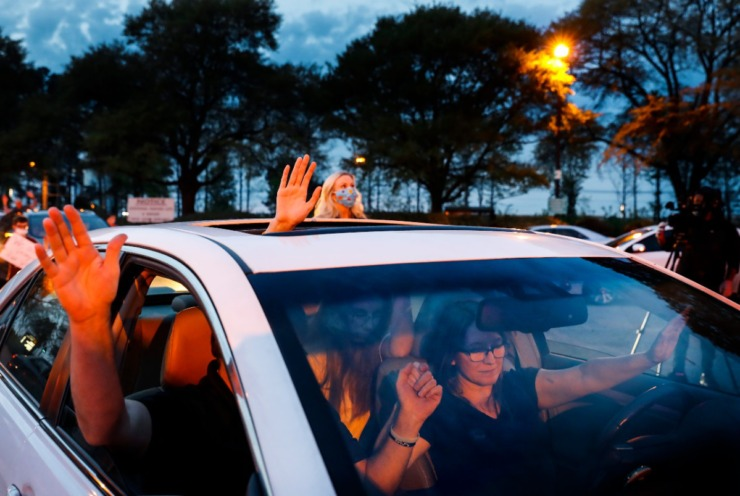 <strong>Nancy Dawson (right) raisers her hand in praise with family members while attending a prayer vigil in the hospital parking lot for patients and staff on Monday, April 6, 2020.</strong> (Mark Weber/Daily Memphian)