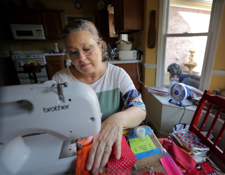 <strong>Laurie Moorhead works on one of the hundreds of homemade masks she has sewn inside her Collierville home while her dog Auggie watches from the window. Moorhead, a retired school teacher who loves to sew, has made nearly 500 masks so far.</strong> (Patrick Lantrip/Daily Memphian)