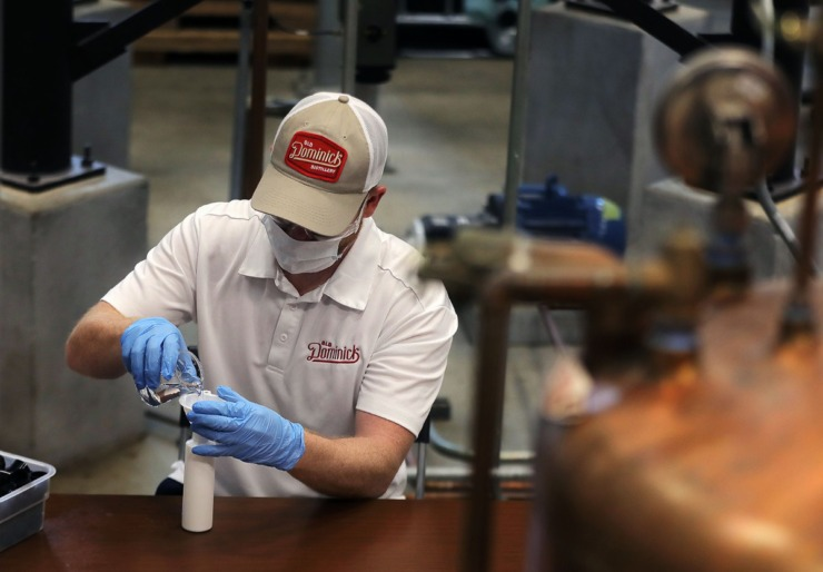 <strong>An Old Dominick Distillery employee pours a fresh batch of hand sanitizer into six-ounce bottles April 7, 2020. The sanitizer is being produced at the Downtown distillery thanks to an emergency resolution from the Shelby County Commission.</strong> (Patrick Lantrip/Daily Memphian)