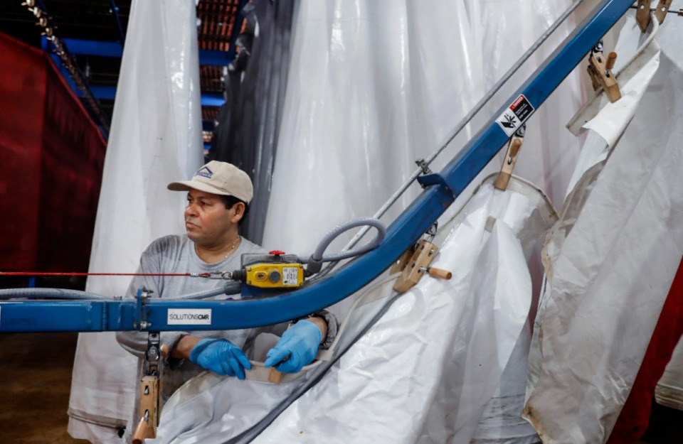 <strong>Mahaffey employee Victor Garcia hangs wet vinyl tent pieces to be dried on Wednesday, April 8, 2020. The local company is shipping various size tents for hospitals across the country to help provide additional spaces for Corvid-19 patients.</strong> (Mark Weber/Daily Memphian)
