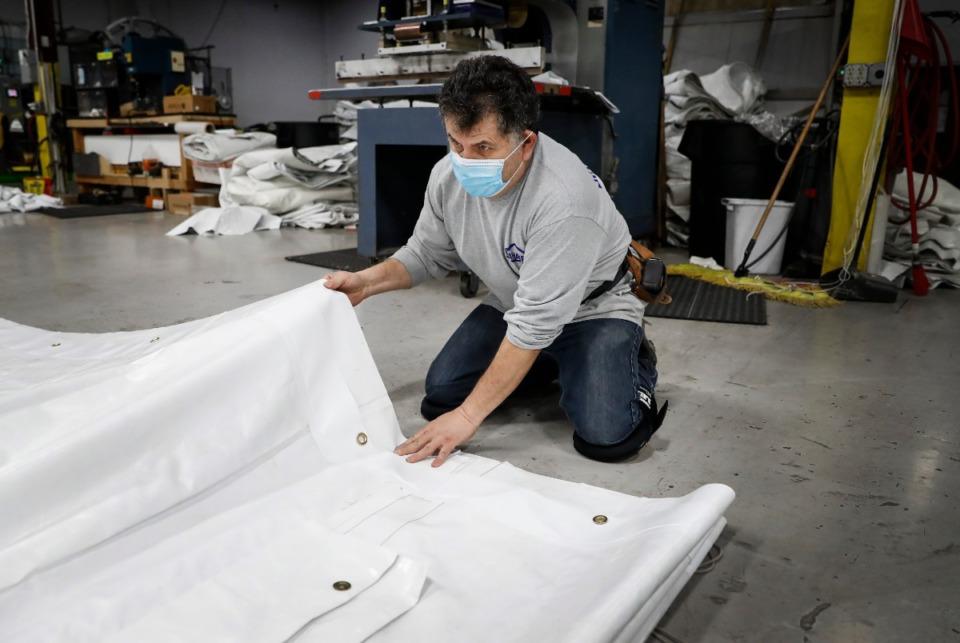 <strong>Mahaffey employee Ruben Soto folds a vinyl tent piece on Wednesday, April 8, 2020.</strong> (Mark Weber/Daily Memphian)