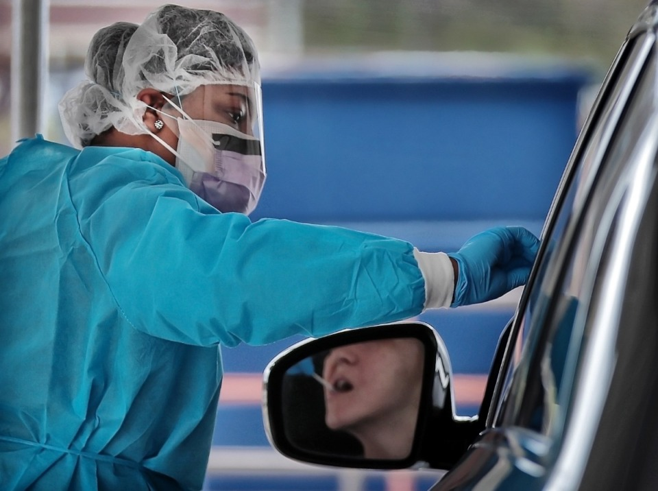 <strong>Registered nurse Shoniece Tate swabs a drive-thru patient during testing on March 21 at a tent behind the Christ Community Health Services clinic. Patients were screened before they could be tested to determine if they had symptoms associated with COVID-19.</strong> (Jim Weber/Daily Memphian)