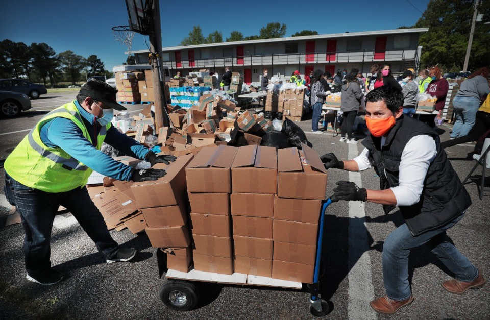 <strong>Jose Manuel Lopez (left) and Jonathan Martinez bring in more food stuffs as some 80 volunteers from Las Americas and Nueva Direccion Church rush to distribute food for 1000 families on April 10, 2020 from the Mid-South Christian College campus. Memphis charities are struggling in the wake of the coronavirus pandemic with donations down over $30 million to date despite the greater need for the services that they provide.</strong> (Jim Weber/Daily Memphian)
