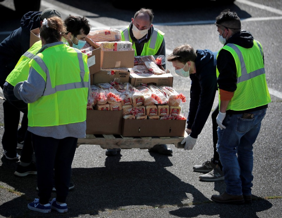 <strong>Some 80 volunteers from Las Americas and Nueva Direccion Church rush to distribute food for 1,000 families on April 10, 2020, from the Mid-South Christian College campus.</strong> (Jim Weber/Daily Memphian)