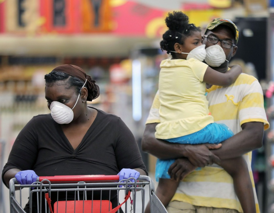 <strong>Tawana Thirsty shops for groceries at the East Memphis Superlo while Martrail Nory holds Myanah Allen on April 8, 2020.</strong> (Patrick Lantrip/Daily Memphian)