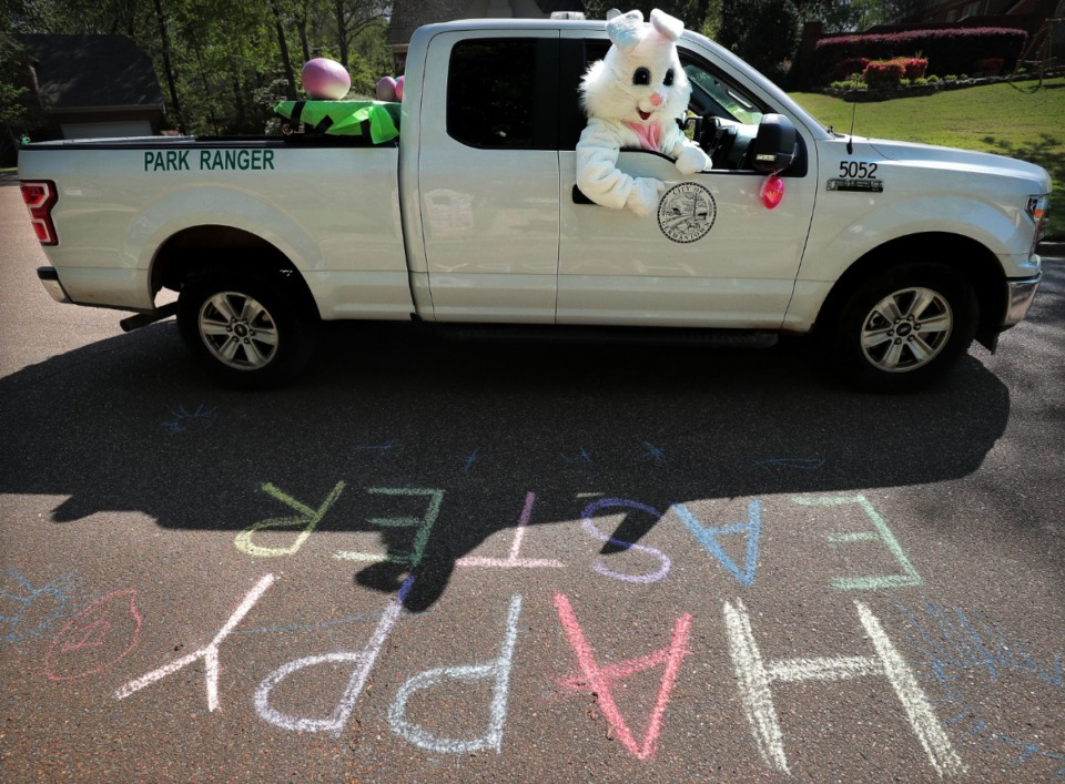 <strong>Volunteer bunny J.D. McMillian checks out an Easter greeting in sidewalk chalk as Germantown Parks and Recreation gave kids their big-bunny fix in an era of social distancing on April 11, 2020.</strong> (Jim Weber/Daily Memphian)