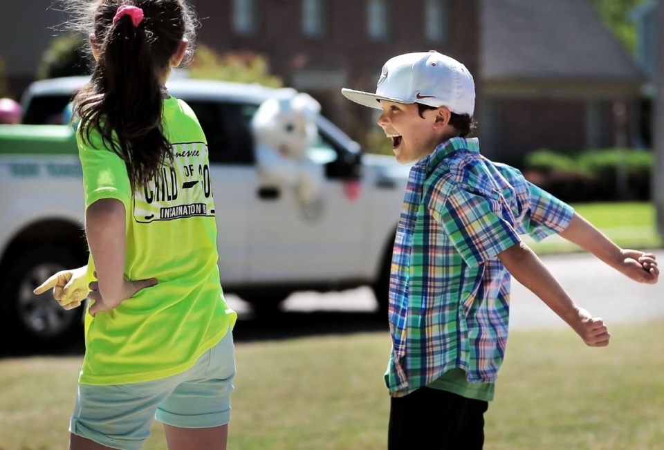 <strong>Giuliana Viotti, 9, and Nicholas Viotti, 7, do a little front-yard-boogie as Germantown Parks and Recreation gives kids their big-bunny fix in an era of social distancing by driving the Easter Bunny around several Germantown neighborhoods on April 11, 2020.</strong> (Jim Weber/Daily Memphian)