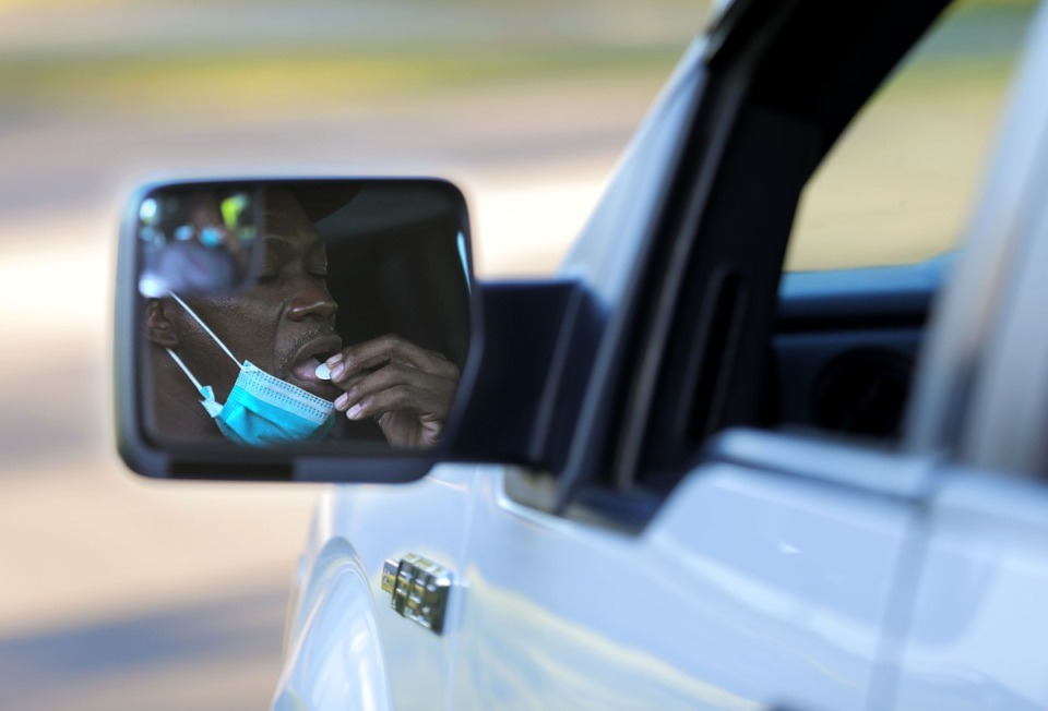 <strong>A member of the Cathedral of Praise church lowers his mask to receive communion during the church's Good Friday Drive-Thru Communion service April 10, 2020.</strong> (Patrick Lantrip/Daily Memphian)