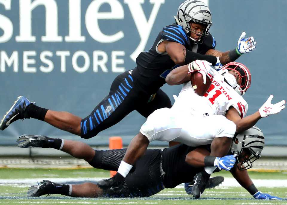 "<strong>Houston Cougars running back Patrick Carr (21) is brought down by two Memphis Tigers defensive backs&nbsp;</strong><span class=""s1""><strong>during the matchup Friday, Nov. 23, at Liberty Bowl Memorial Stadium. </strong>(Houston Cofield/Daily Memphian)</span>"