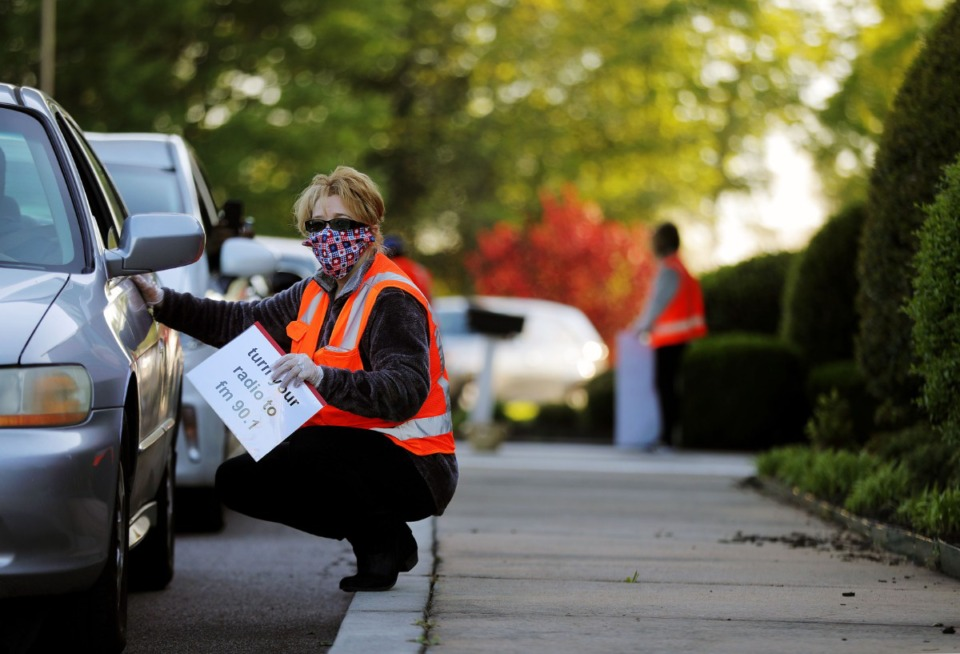 <strong>Pam Elkin helps direct traffic during the Cathedral of Praise's Good Friday Drive-Thru Communion service April 10, 2020.</strong> (Patrick Lantrip/Daily Memphian)