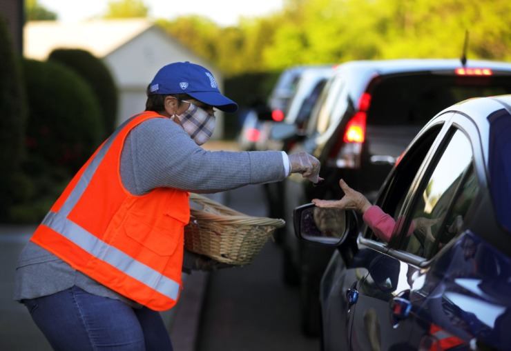 <strong>Stephanie Scoot hands out individual communion packets to parishioners of the Cathedral of Praise's Good Friday Drive-Thru Communion April 10, 2020.</strong> (Patrick Lantrip/Daily Memphian)