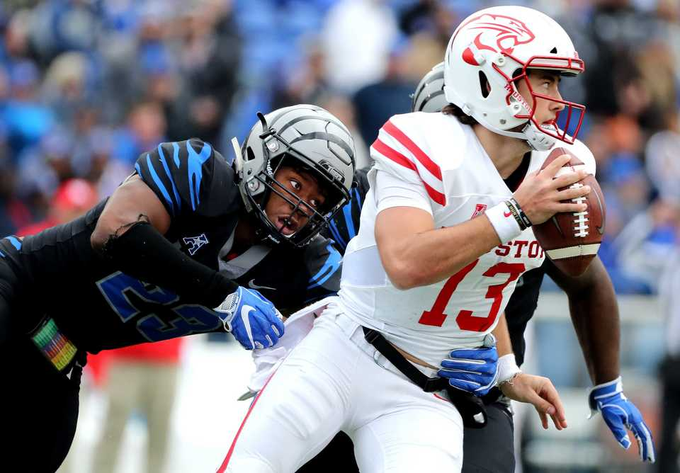 "<strong>Houston quarterback Clayton Tune (13) is sacked by University of Memphis linebacker JJ Russell (23)&nbsp;<span class=""s1"">during the matchup Friday, Nov. 23, at Liberty Bowl Memorial Stadium.&nbsp;</span></strong>(Houston Cofield/Daily Memphian)"