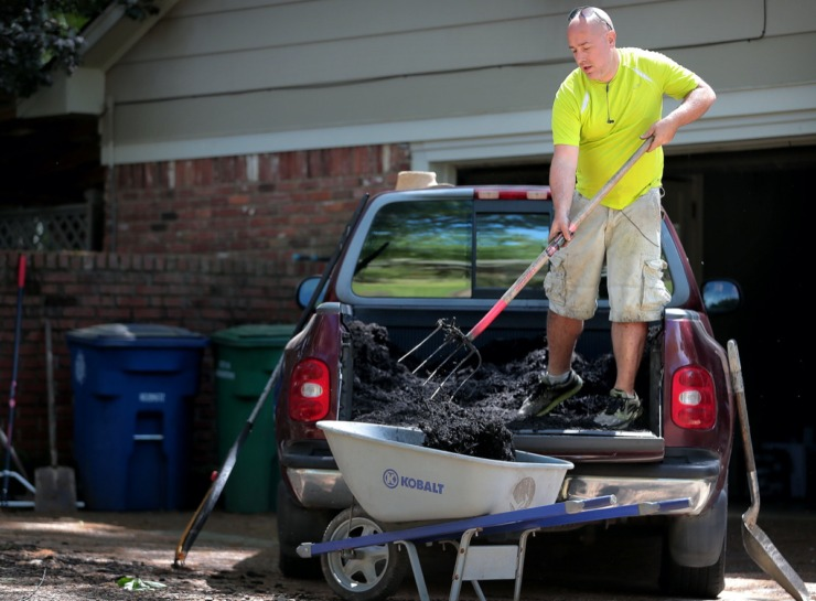 <strong>Scott Briggs shovels mulch out of the back of his borrowed truck while planting hydrangeas at a client's home in East Memphis on April 11, 2020. Briggs is a laid off bartender who, rather than pulling unemployment, decided to start a lawn care business called Laid Off Lawncare, which has exploded with business during its first two weeks.</strong> (Jim Weber/Daily Memphian)