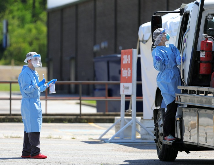 <strong>Health care workers get creative with an oversized vehicle at Christ Community Health's drive-thru COVID-19 testing site in Whitehaven on April 13, 2020.</strong> (Patrick Lantrip/Daily Memphian)