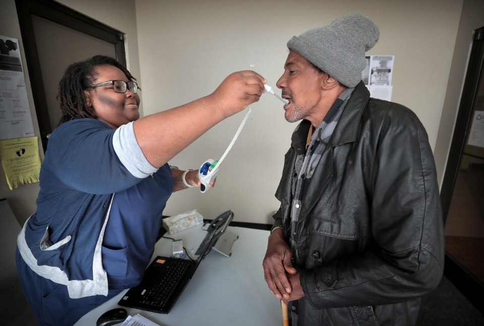 <strong>David Stokes (right) gets his temperature taken by Crystal Brown who screens all patients at the Cherokee Healthcare clinic in Frayser on April, 14, 2020 which is providing COVID-19 testing in the neighborhood for current and new patients. The Cherokee clinic has set aside a designated space and PPE for healthcare workers to cope with patients who are showing virus symptoms.</strong> (Jim Weber/Daily Memphian)