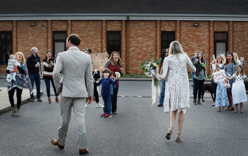 <strong>Holly Whittle and John Steinert are cheered after their wedding by friends practicing social distancing on Saturday, March 21, 2020 at St. Louis Catholic Church.</strong> (Mark Weber/Daily Memphian)
