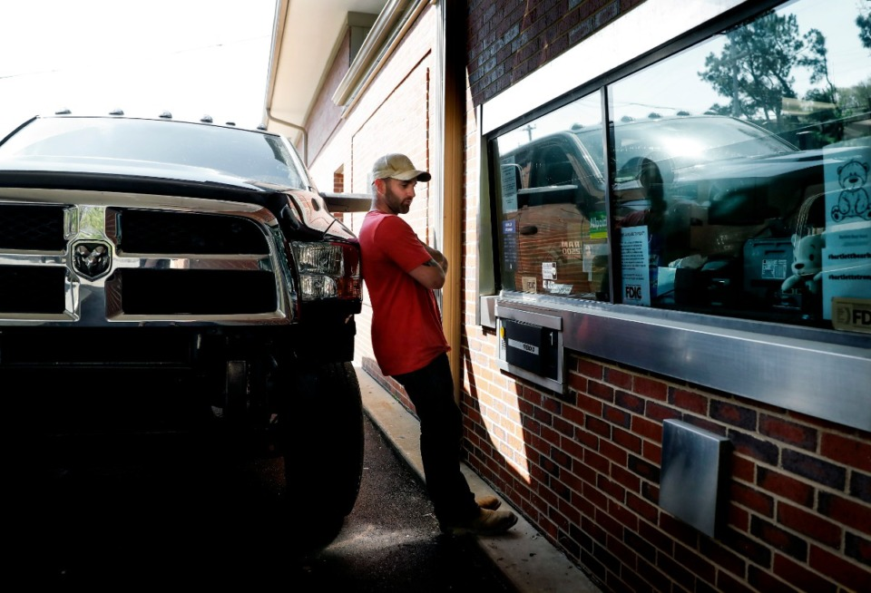 <strong>Bank of Bartlett customer Justin Waldrup waits for service at the drive-thru teller on March 26, 2020, on Stage Road. The height of Waldrup's 4x4 truck made difficult sit in his car for service. The bank closed its doors to customers to adhere to social distancing guidelines due to the coronavirus outbreak.</strong> (Mark Weber/Daily Memphian)