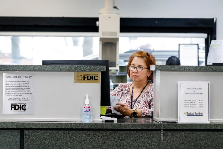 <strong>Bank of Bartlett teller Avelina Lapina counts money for drive-thru customers March 26, 2020, on Stage Road.</strong> (Mark Weber/Daily Memphian)