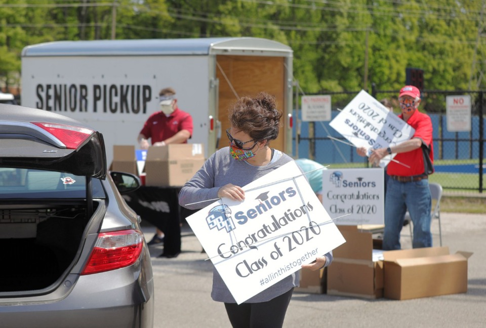<strong>Amy Lovinelli loads up a yard sign in the trunk of a St. Benedict Academy class of 2020 parent while picking up their child's cap and gown April 17, 2020.</strong> (Patrick Lantrip/Daily Memphian)