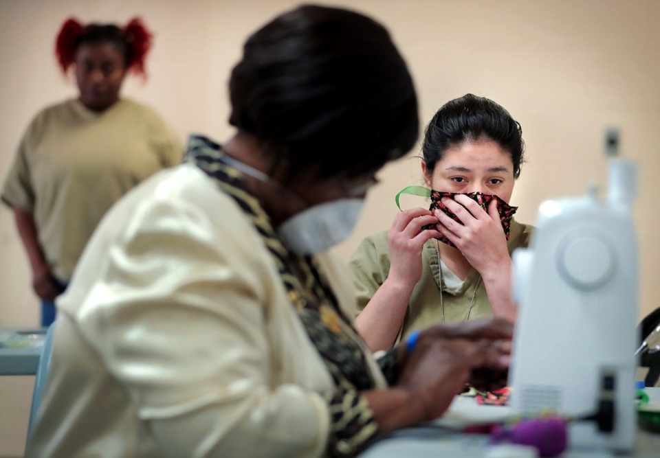 <strong>Savannah Sauceda tries on a mask as inmates at the Shelby County Correctional Center learn how to make fabric masks on April, 17, 2020, in the midst of the coronavirus pandemic. They have one sewing machine now, but Corrections Division Director Anthony Alexander said they hope to have 10 machines up and running soon to produce several hundred masks a week for staff, inmates and community partners like the YWCA.</strong> (Jim Weber/Daily Memphian)