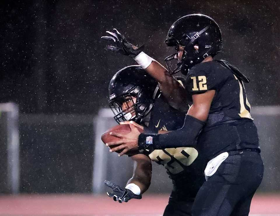 <strong>Whitehaven quarterback Keyshawn Harris hands off to Jackson Fisher in the pouring rain during Whitehaven's state Class 6A semifinal playoff game against Ravenwood at Whitehaven High on Nov 23, 2018.</strong> (Jim Weber/Daily Memphian)