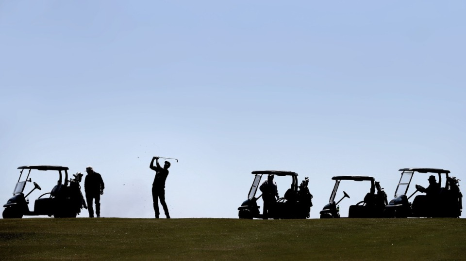 <strong>Michale Kruckman (center) hits from the fairway while playing a game of Texas skins as golfers return to the Links at Whitehaven golf course on April 18, 2020, on a trial basis to test whether golfers would adhere to social distancing requirements during play. Only one person was permitted per cart and golfers were not allowed to handle the flag. (</strong>Jim Weber/Daily Memphian)
