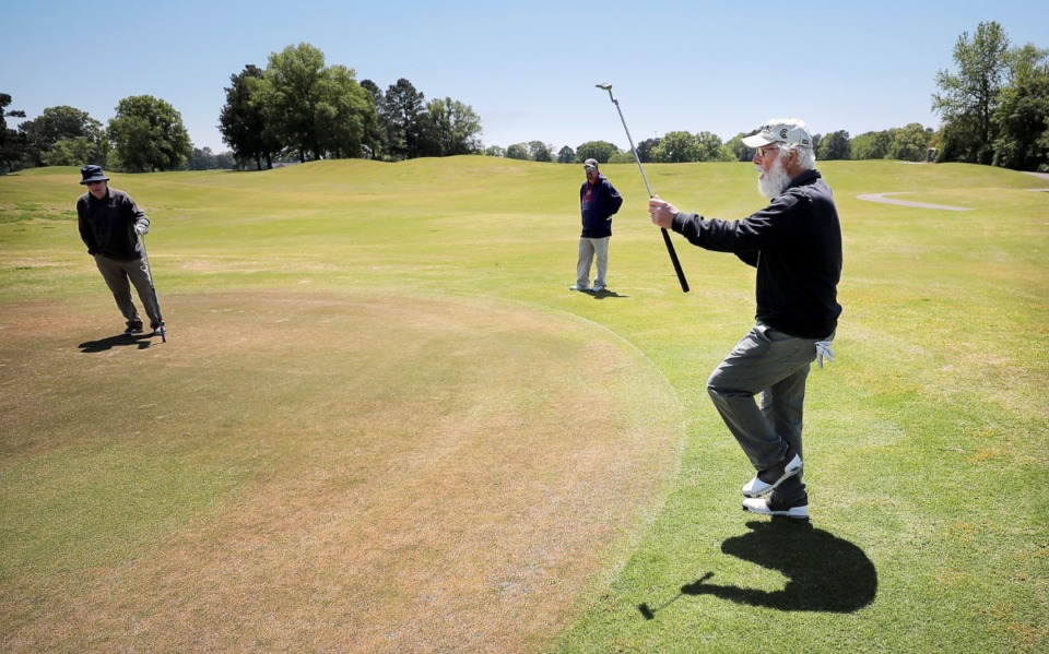 <strong>Lou Albonetti (right) reacts to a missed putt while Bill Sheppard (left) and Ray Duncan watch on from the edge of the green as golfers return to the Links at Whitehaven golf course on April 18, 2020, on a trial basis to test whether golfers would adhere to social distancing requirements during play. Only one person was permitted per cart and golfers were not allowed to handle the flag.</strong> (Jim Weber/Daily Memphian)