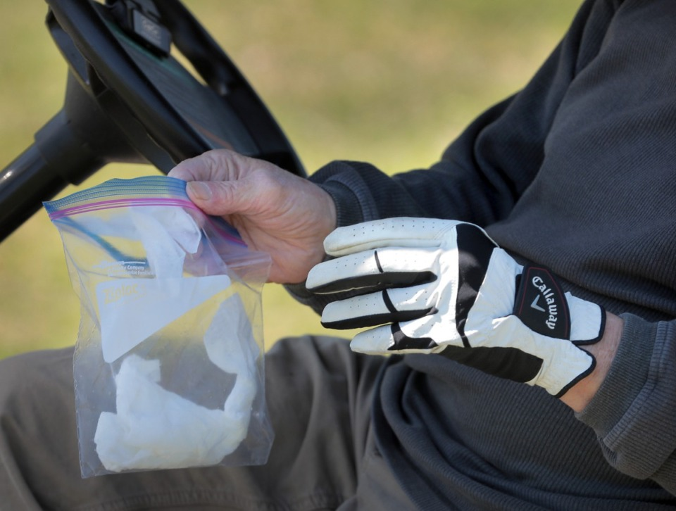 <strong>Bill Sheppard pulls out a bag of disinfectant wipes between holes as golfers return to the Links at Whitehaven golf course on April 18, 2020, on a trial basis to test whether golfers would adhere to social distancing requirements during play. Only one person was permitted per cart and golfers were not allowed to handle the flag.</strong> (Jim Weber/Daily Memphian)