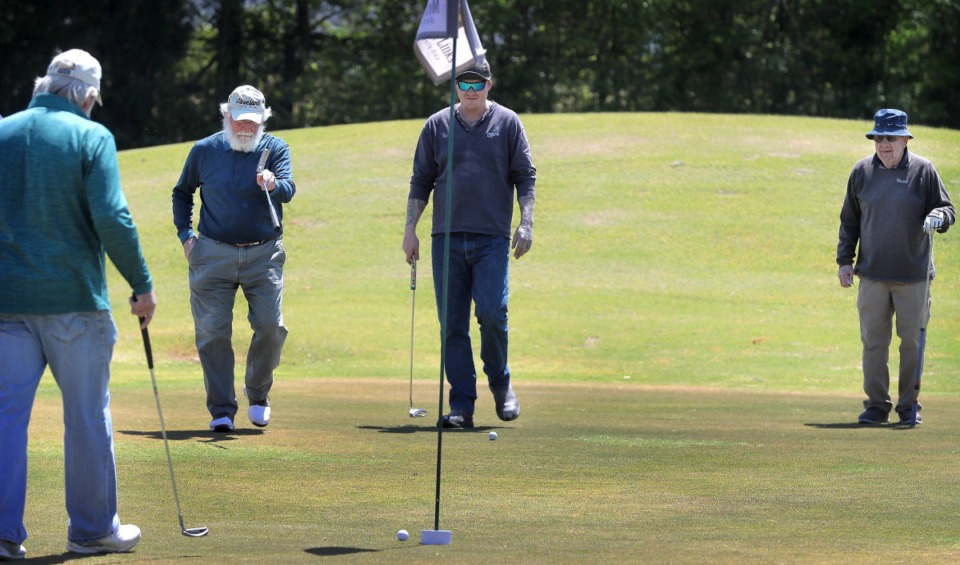 <strong>Lou Albonetti (second from left) reacts to a missed putt while Don Bumpous (left), Michael Kruckman and Bill Sheppard (right) watch from the edge of the green as golfers return to the Links at Whitehaven golf course on April 18, 2020, on a trial basis to test whether golfers would adhere to social distancing requirements during play. Only one person was permitted per cart and golfers were not allowed to handle the flag.</strong> (Jim Weber/Daily Memphian)