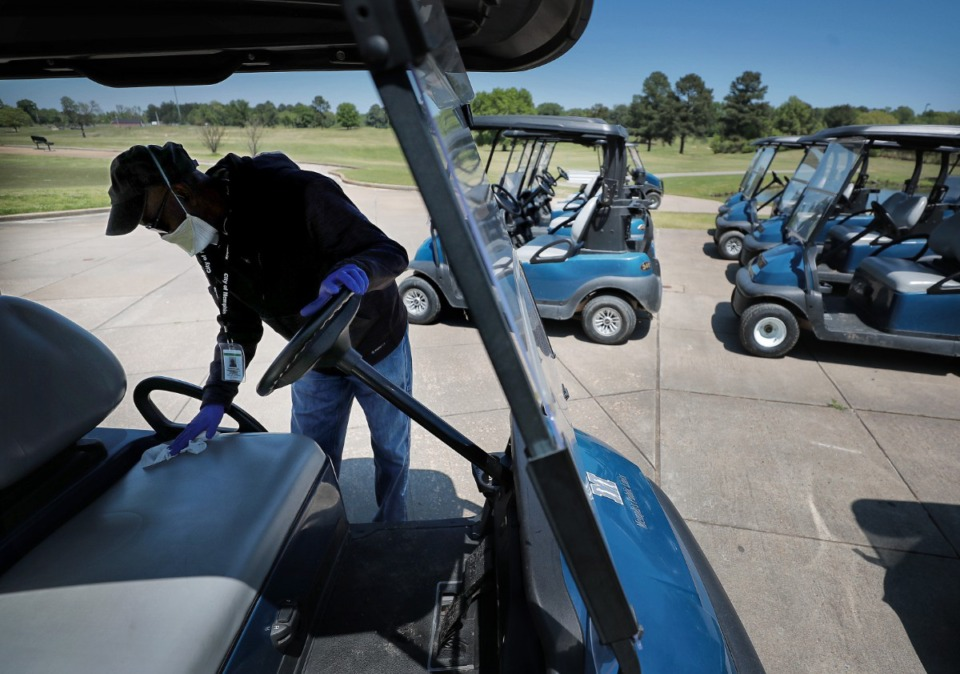 <strong>Clubhouse attendant Thomas Laws disinfects golf carts as golfers return to the Links at Whitehaven golf course on April 18, 2020, on a trial basis to test whether golfers would adhere to social distancing requirements during play. Only one person was permitted per cart and golfers were not allowed to handle the flag.</strong> (Jim Weber/Daily Memphian)