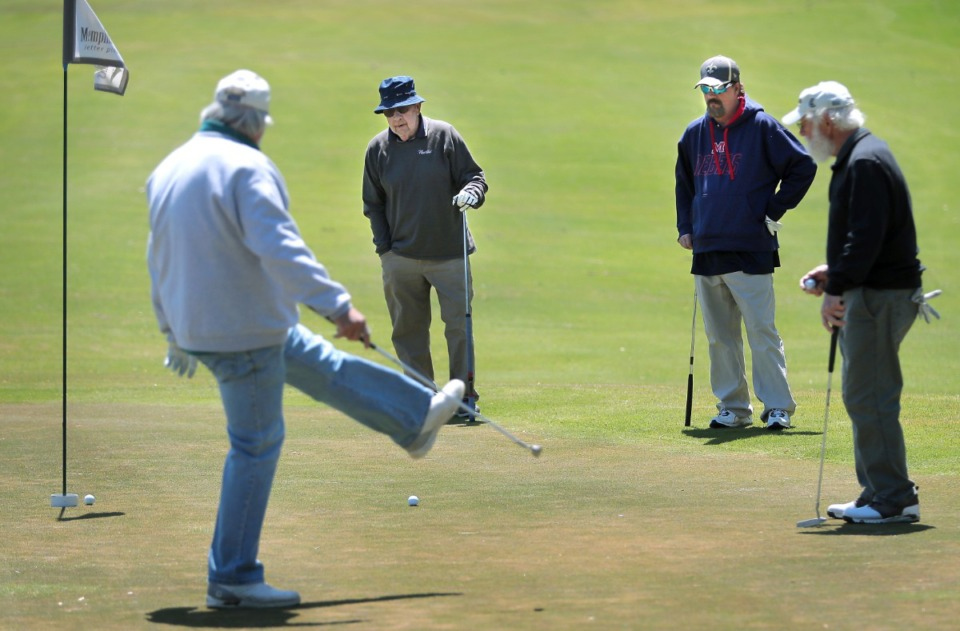 <strong>Don Bumpous (left) reacts to a missed putt while Bill Sheppard, Ray Duncan and Lou Albonetti (right) watch from the edge of the green as golfers return to the Links at Whitehaven golf course on April 18, 2020, on a trial basis to test whether golfers would adhere to social distancing requirements during play. Only one person was permitted per cart and golfers were not allowed to handle the flag.</strong> (Jim Weber/Daily Memphian)