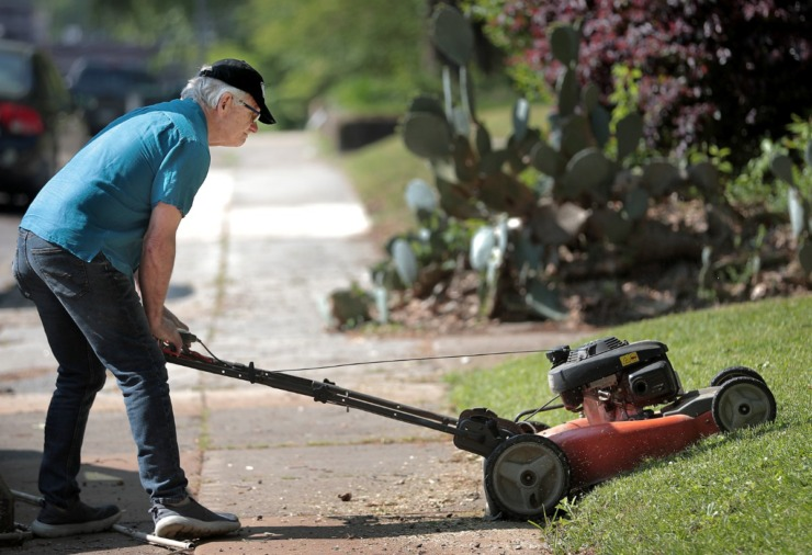 <strong>Sam Goff, mowing his home Saturday, April 18, 2020, said says his Midtown neighborhood's&nbsp; general walkability encourages more foot traffic.</strong> (Jim Weber/Daily Memphian)