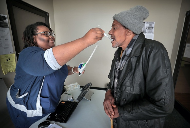 <strong>Crystal Brown (left), who screens all patients at the Cherokee Healthcare clinic in Frayser, takes David Stokes' temperature on April, 14, 2020. The clinic is providing COVID-19 testing in the neighborhood for current and new patients. The Cherokee clinic has set aside a designated space and PPE for healthcare workers to cope with patients who are showing virus symptoms.</strong> (Jim Weber/Daily Memphian)