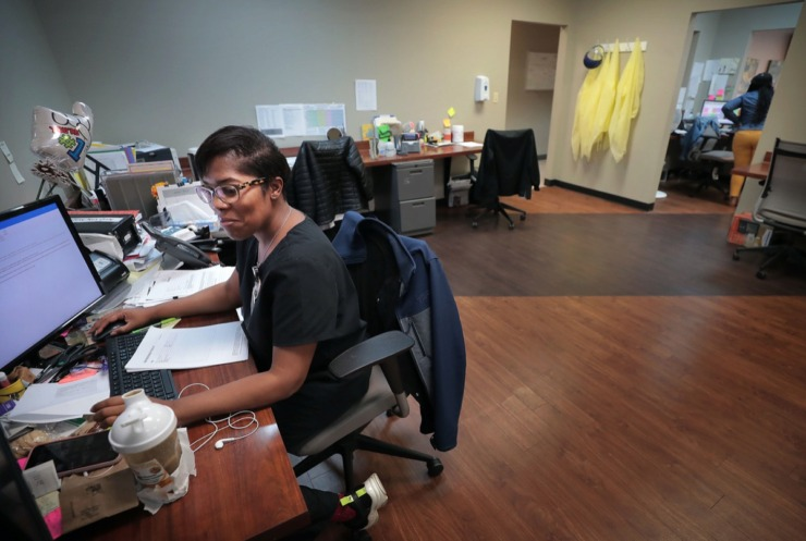 <strong>Tangie Jones helps patients with their prescriptions and health concerns on the telehealth desk at the Cherokee Healthcare clinic in Frayser on April, 14, 2020. The clinic is providing COVID-19 testing in the neighborhood for current and new patients. The Cherokee clinic has set aside a designated space and PPE for healthcare workers to cope with patients who are showing virus symptoms.</strong> (Jim Weber/Daily Memphian)
