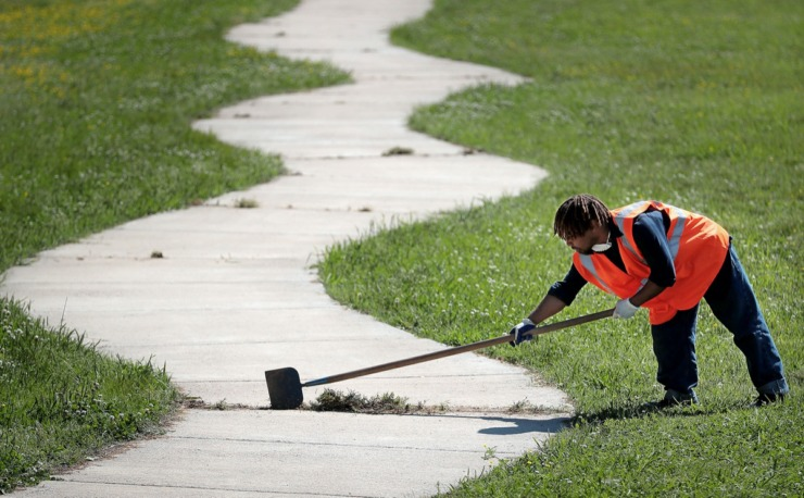 <strong>Sheldon Green of the Heights CDC cleans weeds out of the walking path while performing maintenance at Treadwell Park on April 15, 2020. The Heights CDC is struggling to maintain a full workforce even as it launches a COVID-19 response fund to help neighborhood residents struggling to pay bills.&nbsp;</strong>(Jim Weber/Daily Memphian)