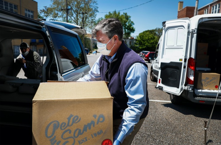 <strong>Catholic Charities of West Tennessee Executive Director Kelley Henderson (middle) helps case manager Shannon Privett (left) load a car with spaghetti diners donated from Pete and Sam's restaurant on Wednesday, April 15, 2020. Pete and Sam's donated 560 meals to be part of care packages delivered to 160 formerly homeless families. Some of the donated meals will also be handed out to several area churches, which also help feed needy and homeless families.</strong> (Mark Weber/Daily Memphian)