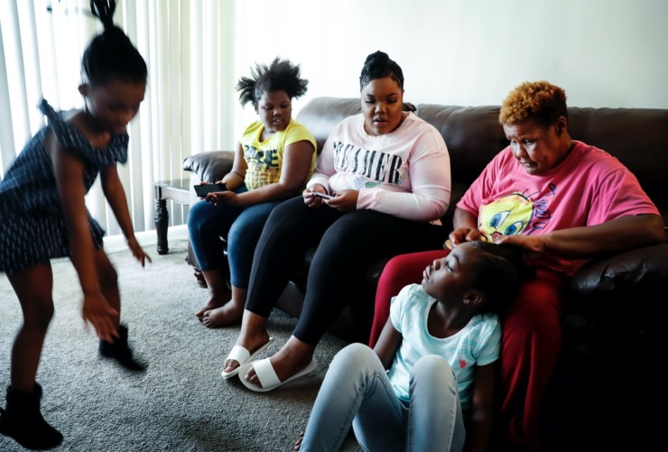 <strong>Beverly Robinson (right, pink shirt) works on the hair of her daughter Kensley Robinson, 10, as her other daughter Kentara Robinson, 17, (middle) and granddaughters Krystal Cole, 8 (second left), and Kelsey Robinson, 5, play on their phones or dance in their Hickory Hill apartment on Wednesday, April 15, 2020. In Shelby County, 71% of those who test positive for COVID-19 are African Americans.</strong> (Mark Weber/Daily Memphian)