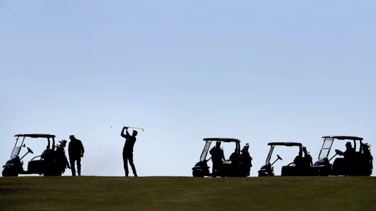<strong>Michale Kruckman (center) hits from the fairway while playing a game of Texas skins as golfers return to the Links at Whitehaven golf course on April 18, 2020, on a trial basis to test whether golfers would adhere to social distancing requirements during play. Only one person was permitted per cart and golfers were not allowed to handle the flag.</strong>&nbsp;(Jim Weber/Daily Memphian)