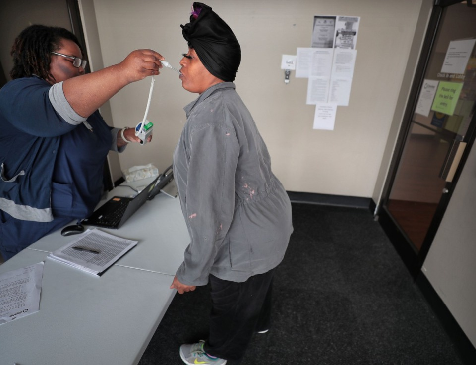 <strong>Tanita Lewis (right) gets her temperature taken by Crystal Brown, who screens all patients at the Cherokee Healthcare clinic in Frayser on April, 14, 2020.</strong> (Jim Weber/Daily Memphian)