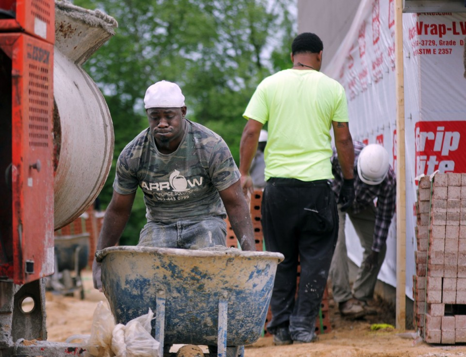 <strong>Carlos Morgan lifts a heavy wheelbarrow full of freshly-mixed wet cement to distribute to his coworkers who are busy laying bricks at a new gas station and strip center that is going up near the intersection of Germantown Parkway and Highway 70 in Bartlett on April 22, 2020.</strong> (Patrick Lantrip/Daily Memphian)