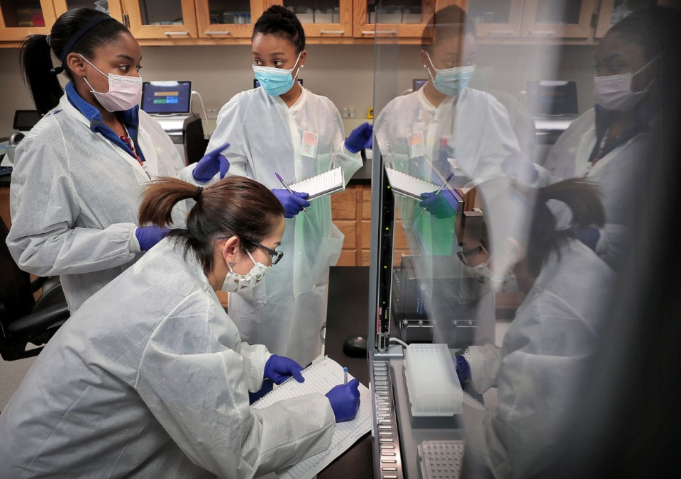 <strong>Medical technicians Jasmine Becton (left), Lanthanh Nguyen and Calisha Beauregard train on a new piece of equipment between processing patient samples at UTHSC's Coronavirus testing lab in the Hamilton Eye Center on April 16, 2020.&nbsp;Shelby County reported 50 new cases Friday, April 24, but also confirmed its highest single day of new tests since Monday, April 20.&nbsp;</strong> (Jim Weber/Daily Memphian file)