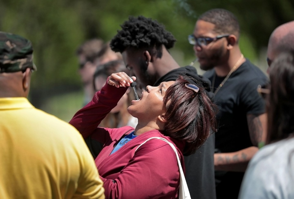 <strong>Iseashia Thomas samples CBD oil, a legal form of marijuana that she hopes will help cure her migraine headaches, during the first Mid-South Hemp Fest at Overton Park on April 20, 2019.</strong> (Jim Weber/Daily Memphian)