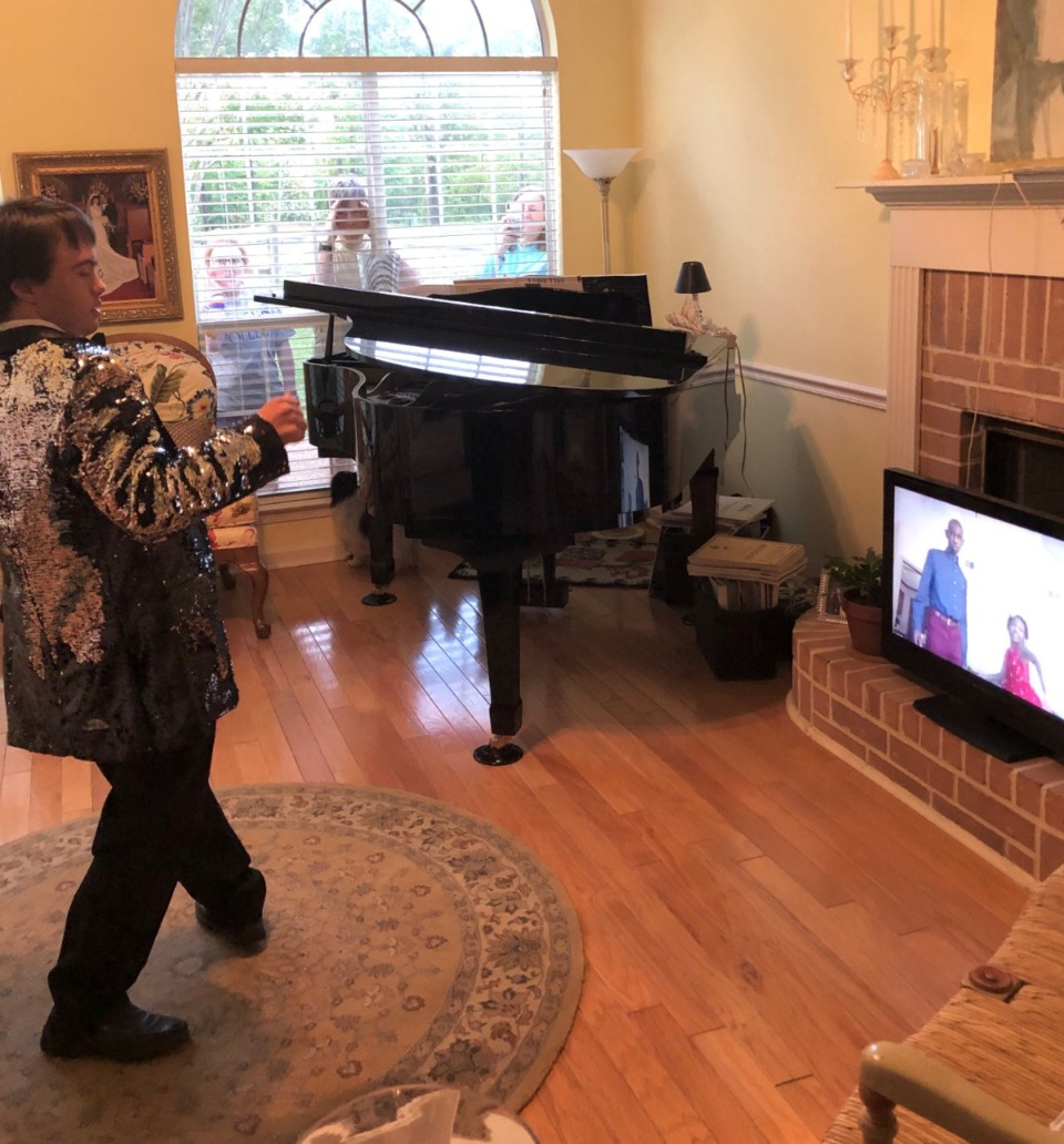 <strong>Ben Halvorson dances during the virtual Madonna Prom as relatives watch through the window.&nbsp;</strong>(Submitted)