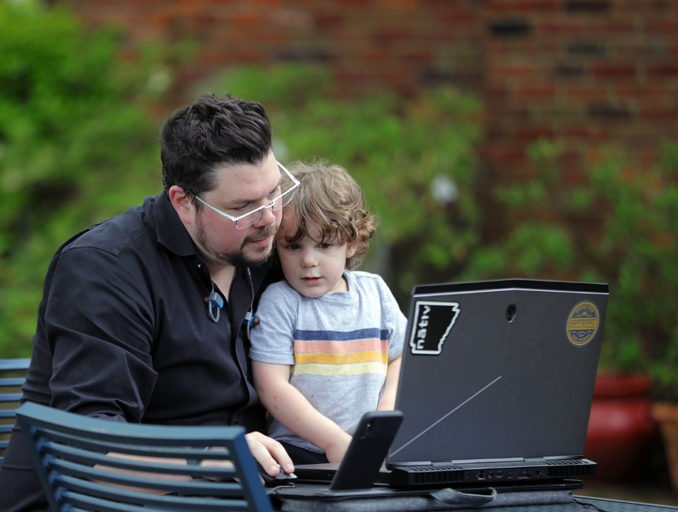 <strong>Architect Jason Jackson of brg3s works on his laptop backyard while entertaining his son Oliver in his East Memphis April 24, 2020.</strong> (Patrick Lantrip/Daily Memphian)