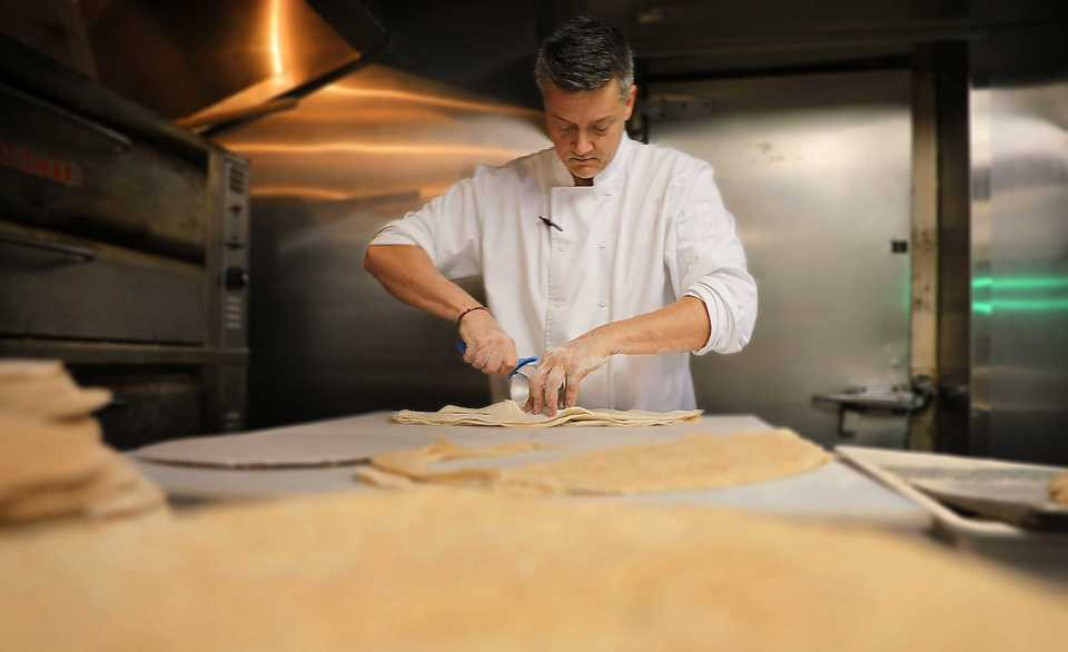 <strong>Chef and co-owner Michael Bomarito prepares the handmade dough used to make the pizzas at Pete &amp; Sam&rsquo;s. The family owned Italian restaurant has been using the same recipe for its dough since 1948.</strong> (Patrick Lantrip/Daily Memphian)