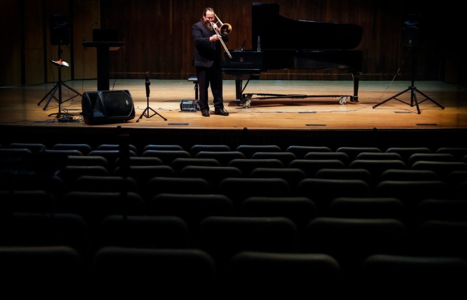 <strong>University of Memphis student Tommy Johnson performs on his trombone to an empty campus theater during his doctorate of musical arts recital on Tuesday, April 28, 2020. Johnson's presentation on famed trombone player Wycliffe Gordon was live-streamed to his advisors and community members.</strong> (Mark Weber/Daily Memphian)