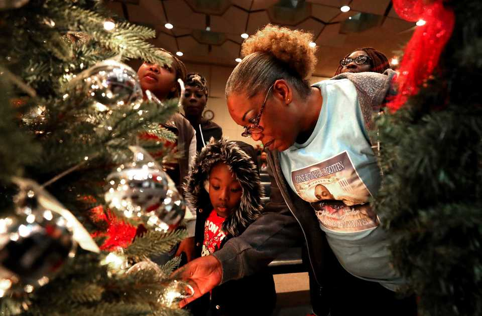 <strong>Cynthia Watson, mother of Christopher Jordan, searches for her son's ornament on the Christmas tree displayed at the Season of Remembrance ceremony Nov. 26. Jordan was one of the 174 victims of domestic violence in Memphis in 2018.</strong> (Houston Cofield/Daily Memphian)