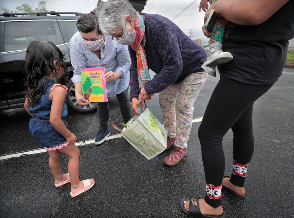 <strong>A four-year-old gets a bag of new books from Edith Ornelas (second from left) and Nicole Davila with the Mariposa Collective as the pair delivers care packages of food, clothes and baby supplies to undocumented immigrant families in Southeast Memphis on April 23, 2020. In the midst of the Coronavirus crisis, Ornelas, a cofounder of the collective, and volunteers visit local families several times a week to provide aid.</strong> (Jim Weber/Daily Memphian)