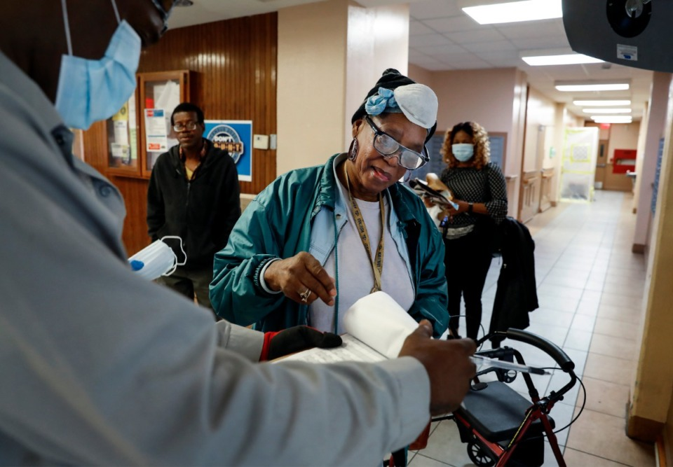 <strong>Memphis Housing Authority resident Constance Lloyd (middle) signs paperwork while receiving a donated face mask on Thursday, April 23, 2020 at Dr. R.Q. Venson Center Apartments.</strong> (Mark Weber/Daily Memphian)